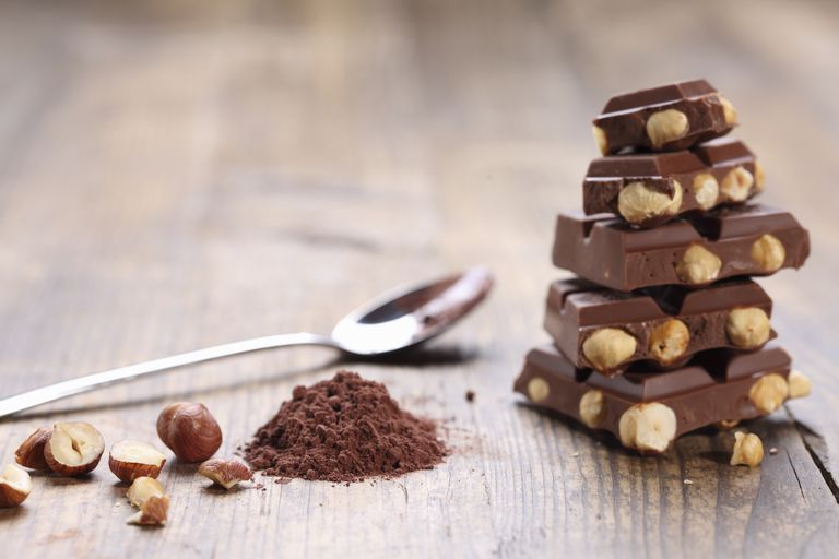 Stacked nut chocolate, cocoa powder and hazelnut, close-up