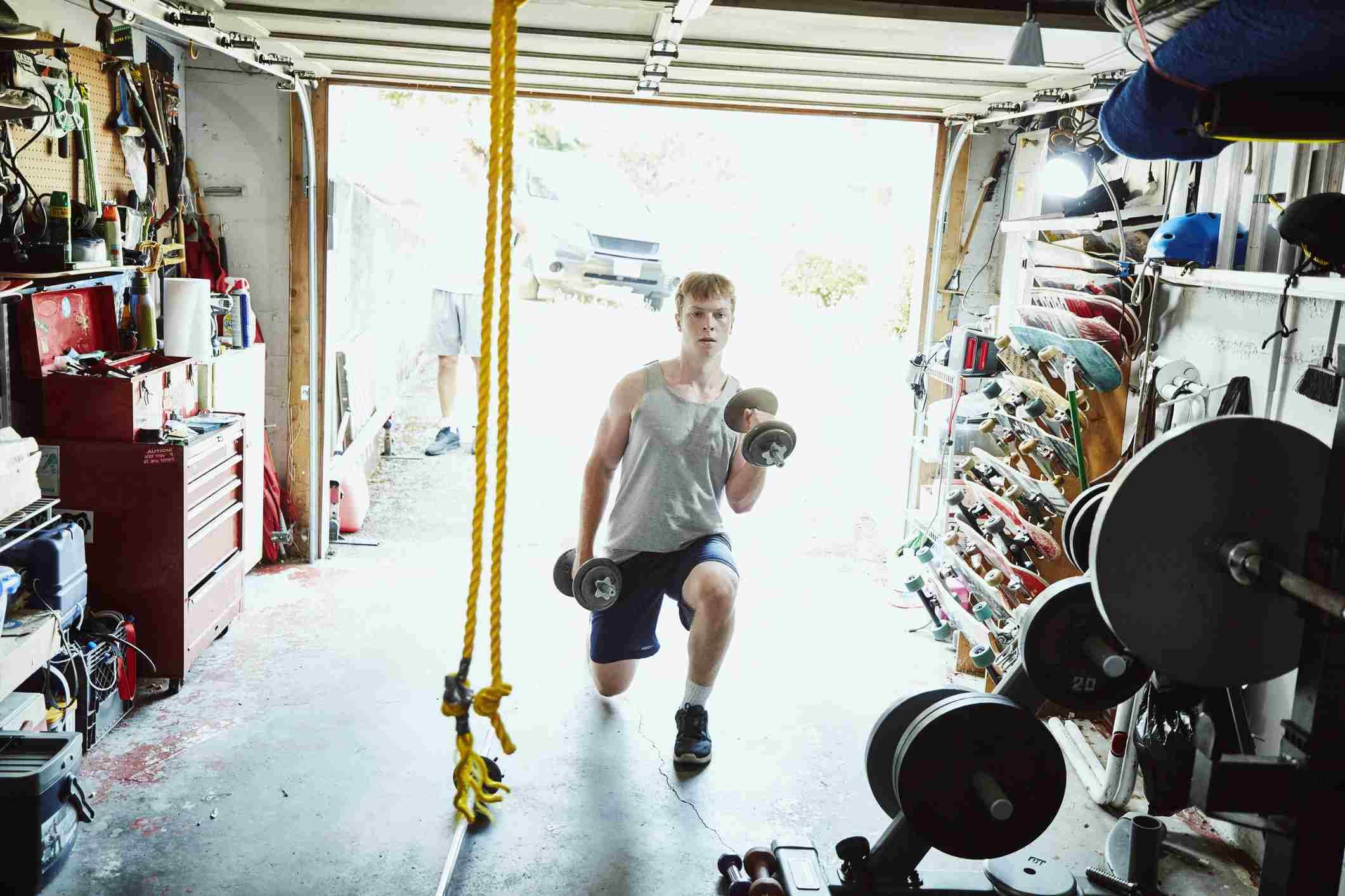 Joven haciendo estocadas con pesas en el gimnasio en el garaje