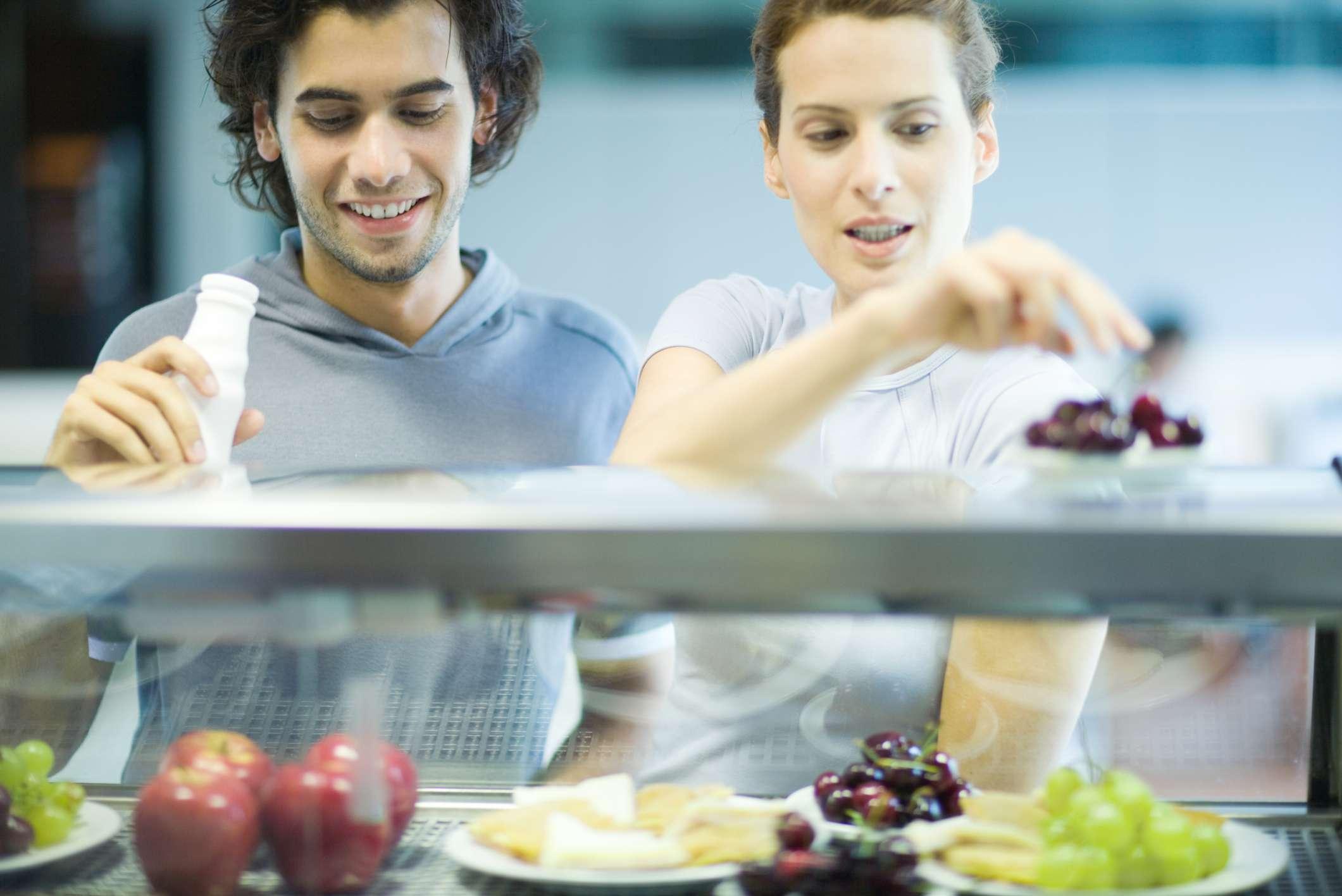 Estudiantes universitarios que eligen alimentos saludables.