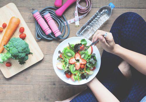 Entrenador de bienestar con alimentos saludables y artículos de fitness.