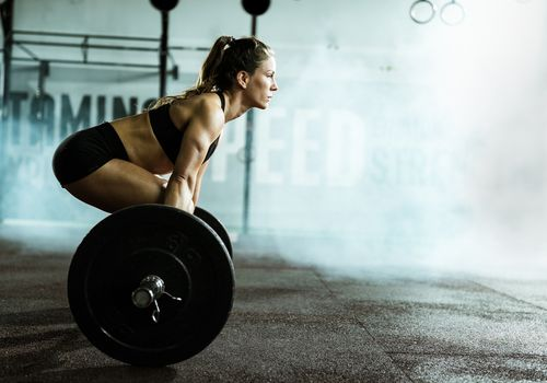 A woman preparing to perform a deadlift with a barbell.