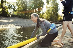 Woman placing paddleboard on river while man standing beside at pier