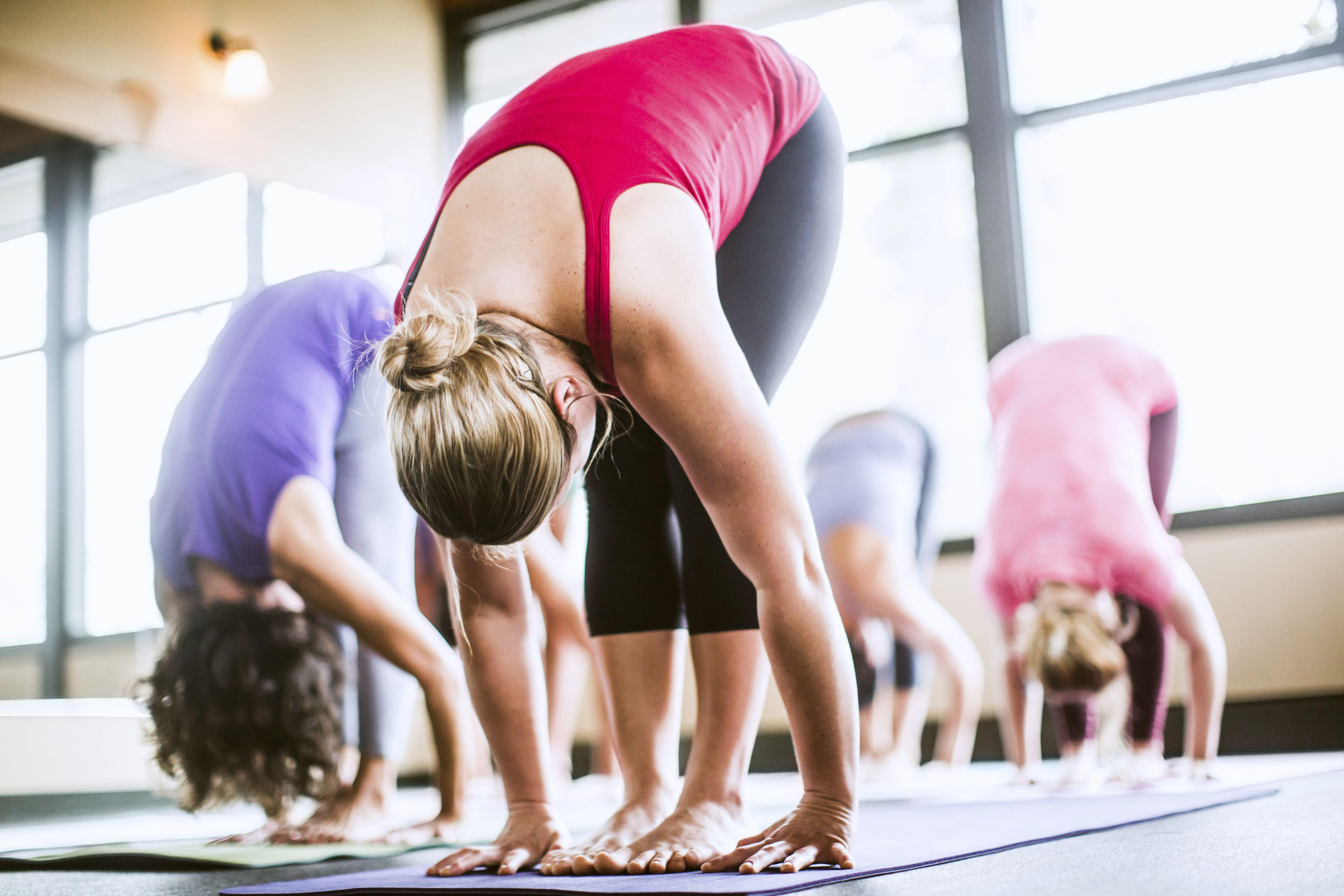 Clase de yoga en flexión hacia adelante (Uttanasana)