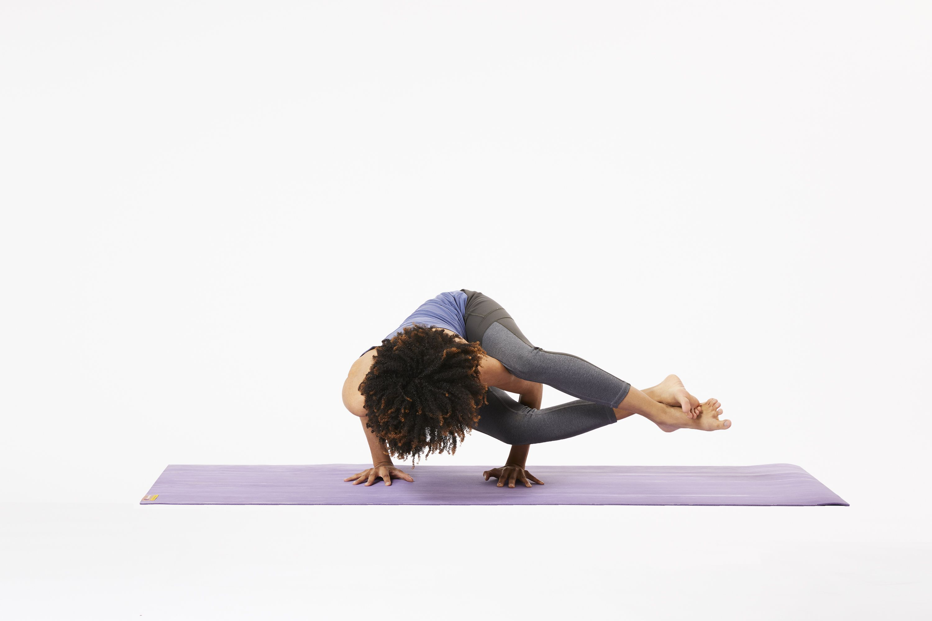 Woman on yoga mat in eight angle pose