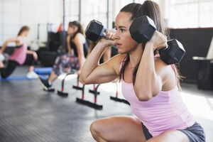 woman doing squats with dumbbells in gym