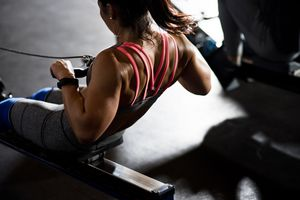 Woman in pink sports bra exercises on a rowing machine.