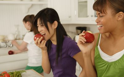 Teenage girls (16-17) with young woman in domestic kitchen, laughing
