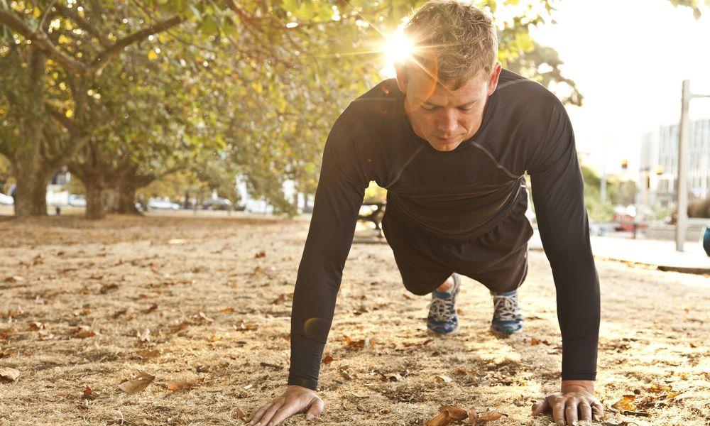 MAN EXERCISING IN PARK DOING PUSH-UPS