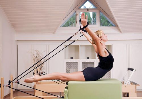 Woman doing an exercise on the Pilates reformer