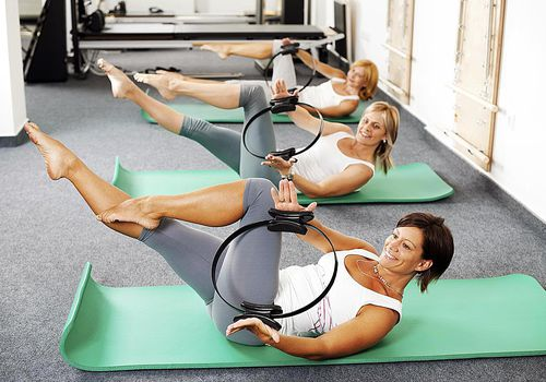 Tres mujeres usando Magic Circles y haciendo Pilates en esteras