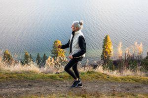 senior woman walking along coastal mountain trail