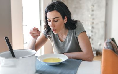 Woman with bowl of soup, blowing on a spoonful, sitting at dining table