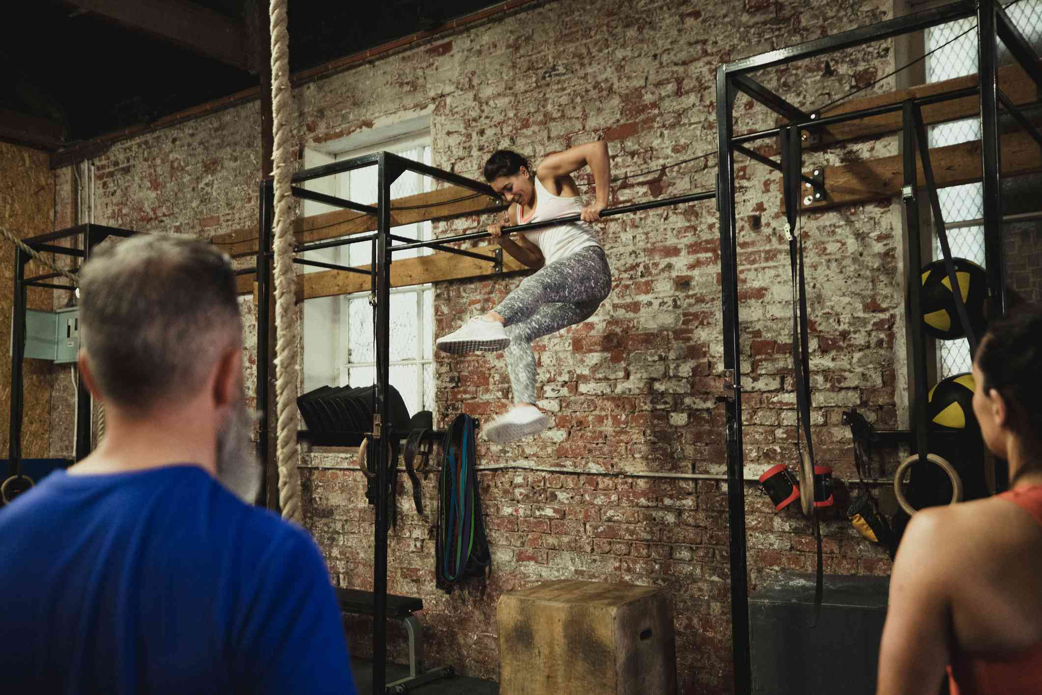 A woman performs a bar muscle-up in a CrossFit gym
