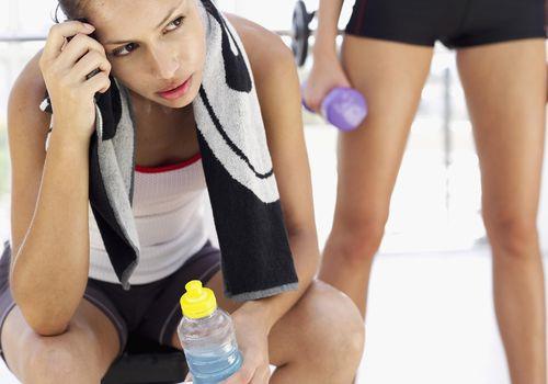 Joven mujer sentada en el gimnasio con una botella de jugo y otra persona detrás de ella
