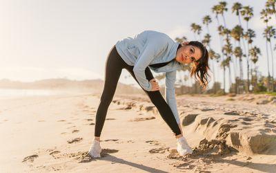 female runner stretching on the beach