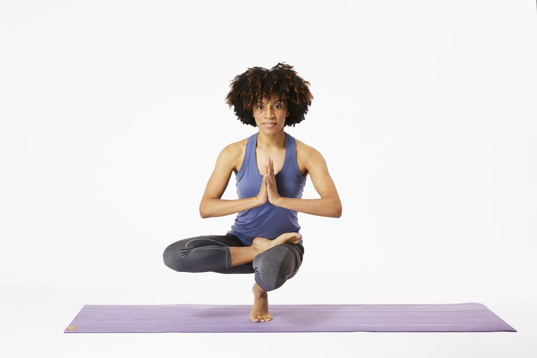 Woman on yoga mat doing toe stand pose