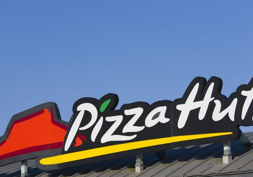 Pizza Hut sign on the roof of a restaurant.