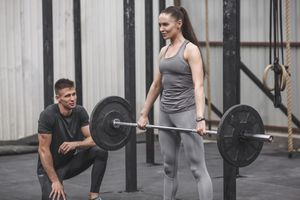 Male instructor looking at young woman training at gym