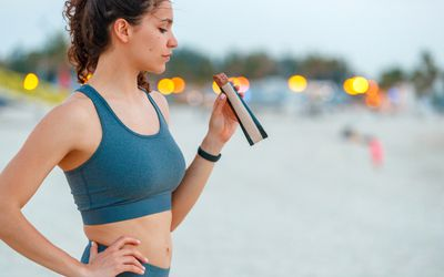 Young woman on a break from jogging, eating protein bar - stock photo