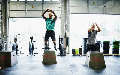 men doing box jumps in crossfit gym
