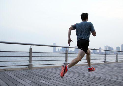Hombre corriendo en el muelle frente al horizonte de la ciudad