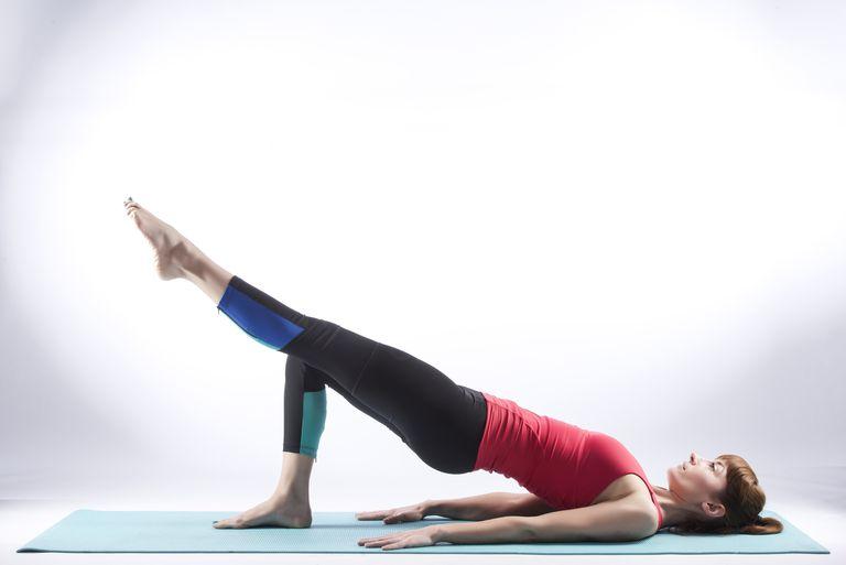 A pilates teacher doing shoulder bridge pilates move