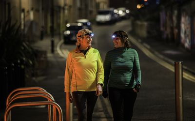Two friends with headlamps walking together at night