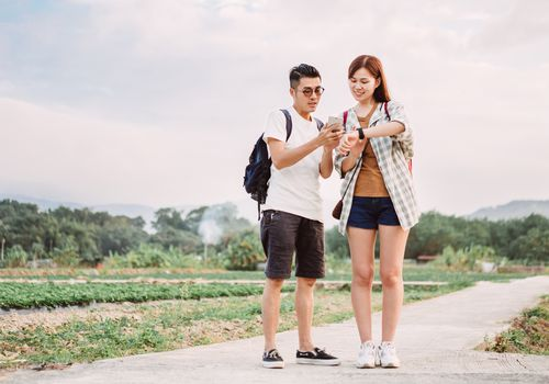 Couple on walking path checking their phone and smartwatch