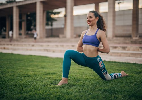 Woman performing the kneeling hip flexor stretch outside