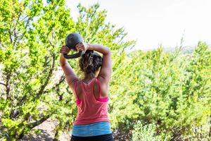Back of young fit woman performing kettlebell halo