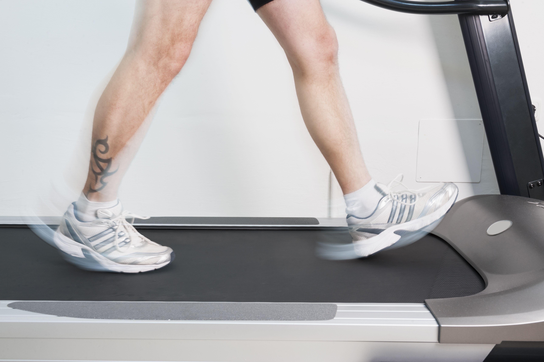 Man's legs walking on a treadmill
