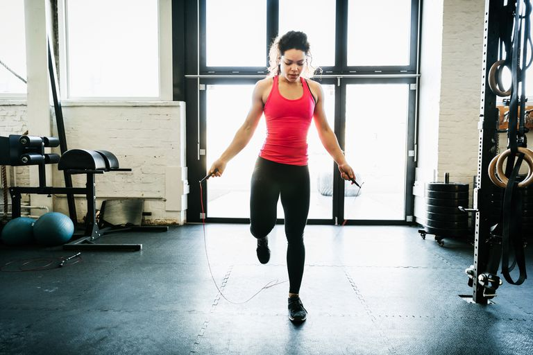 A girl jumps rope in a CrossFit gym.