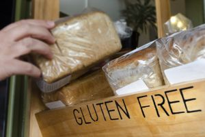 Person picking up a loaf of gluten free bread
