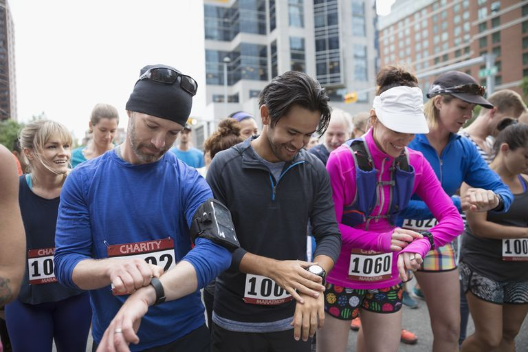 Marathon runners ready, preparing smart watches at starting line on urban street