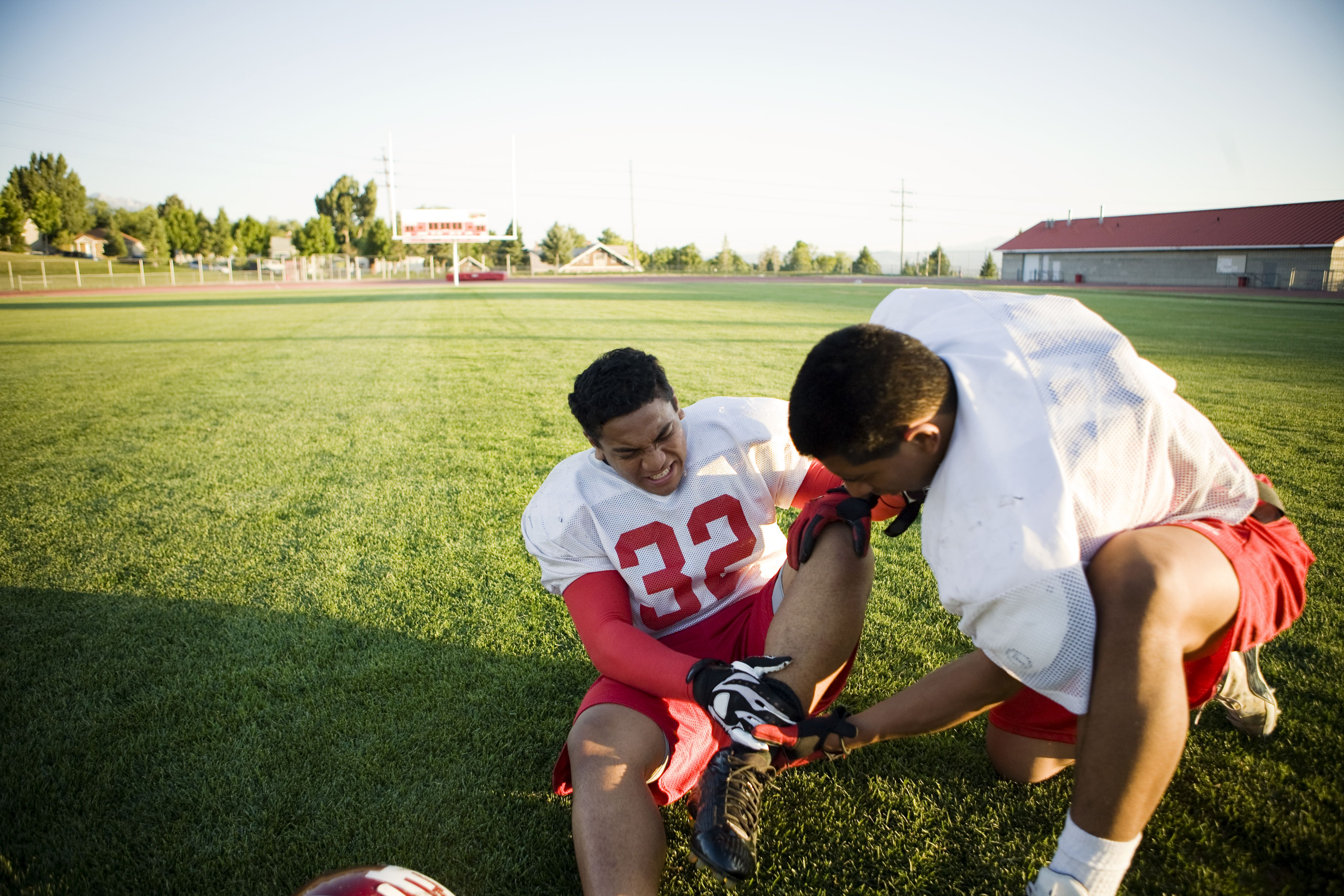 Injured football playing wincing while a teammate looks at his ankle