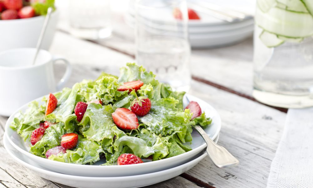 Strawberry caesar salad on a white plate