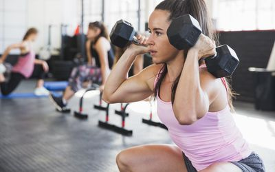Woman doing squats with dumbbells in a gym