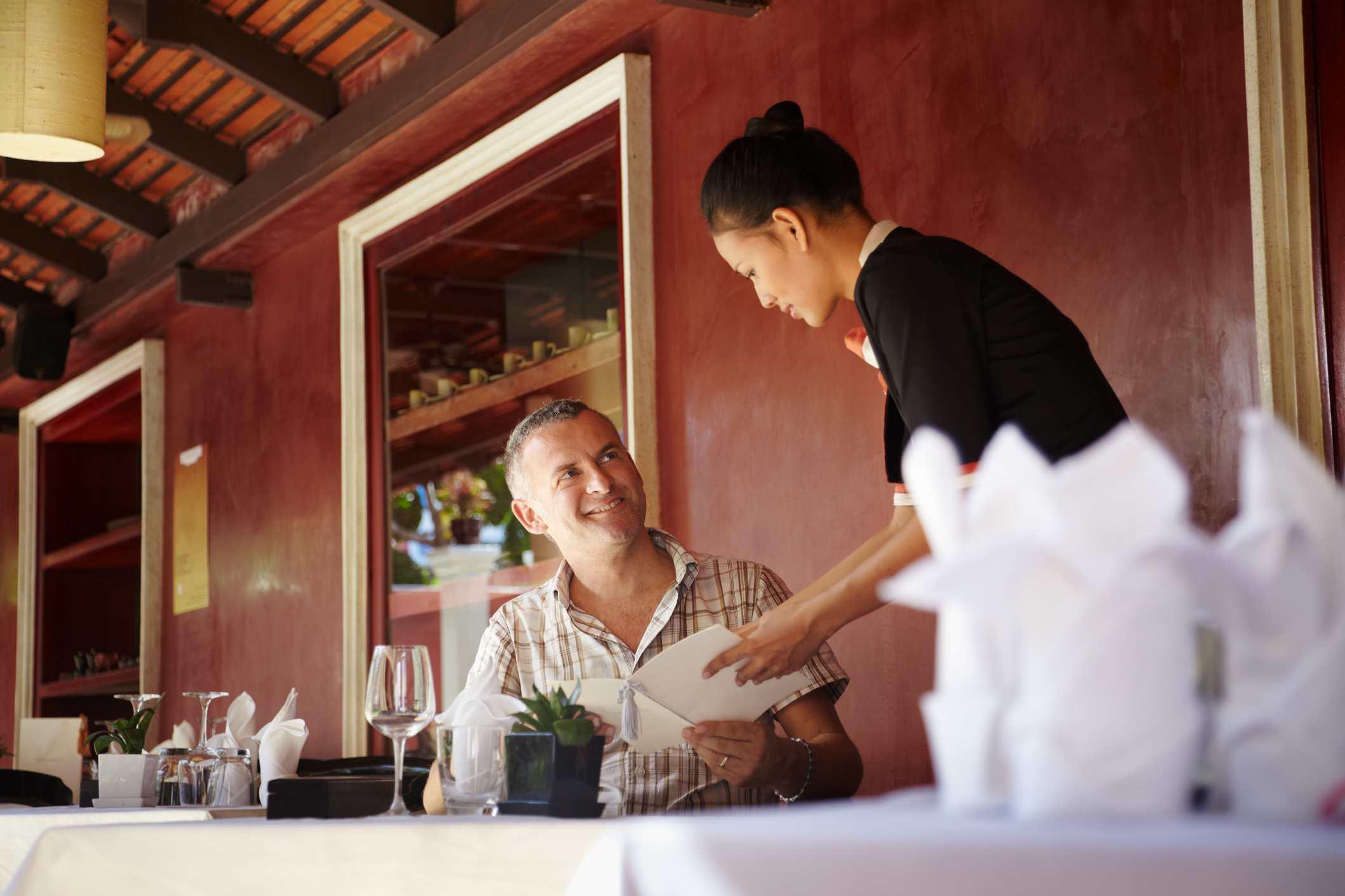 Camarera hablando con el cliente en el restaurante