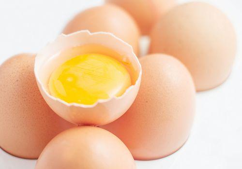 Primer plano de cartón de huevos con huevo roto