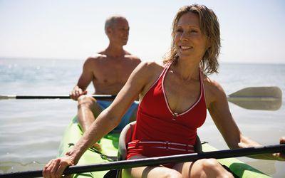 Senior couple in kayak smiling, close-up (focus on woman)