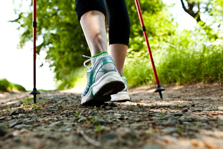 close-up of woman's ankles walking outside with hiking poles