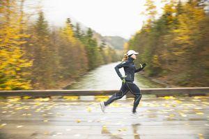 A woman jogging over a bridge in fall