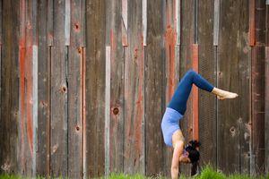 Woman doing inverted yoga pose outside