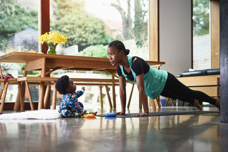 a baby boy sitting in front of a woman in plank position