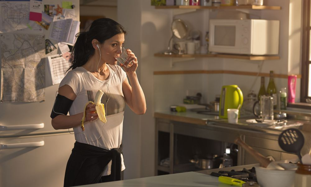 female runner eating and drinking in kitchen before exercise