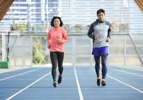 Man and woman running 1 mile on a track