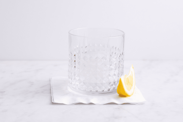Vodka in glass with lemon wedge