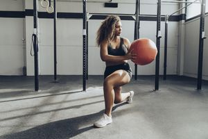 African American woman performing medicine ball exercise