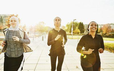 Three women exercising outside.
