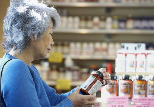 Senior mujer asiática leyendo etiqueta de vitamina